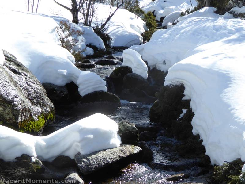 It appears that a sudden rise in water level has carved away the snow pack since my last visit